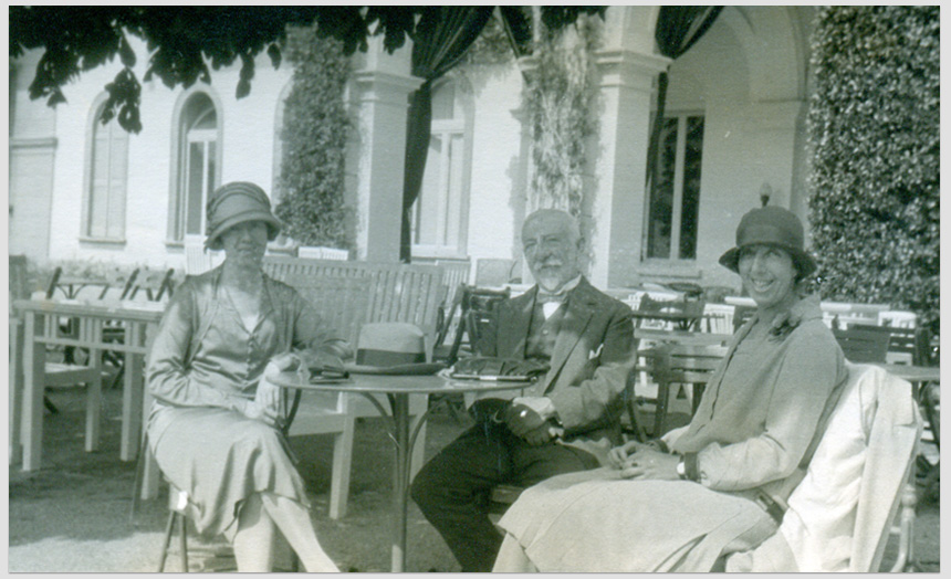 David Edward Theomin with his daughter Dorothy. They are seated at a table with an unidentified woman. This photo forms a black and white postcard, possibly from holiday overseas travel in 1927.
